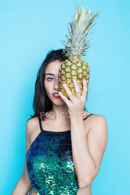 Young woman in glitter top covering eye with pineapple on blue background — Stock Photo