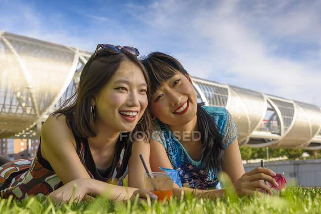 Asiatische Frauen liegen auf Parkrasen — Stockfoto