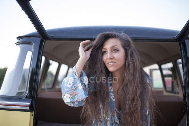 Beautiful and young woman enjoys the trip in her vintage van with some friends — Stock Photo