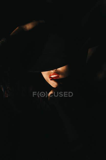 Приваблива молода жінка закриває половину обличчя капелюхом, стоячи у темній кімнаті. — стокове фото