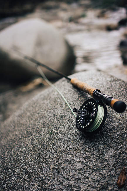 Close-up of fishing rod on smooth boulder on shore in nature — Stock Photo