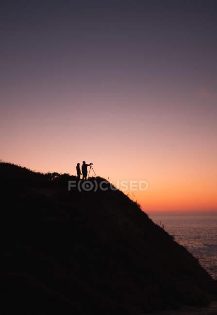 Силует двох людей з камери на штатив стоячи на узбережжі поблизу спокійне море на тлі заходу сонця безхмарне небо — стокове фото