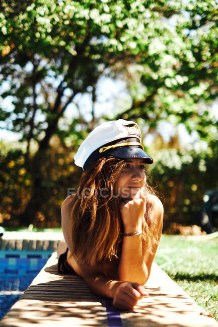Donna in cappello da capitano sdraiata vicino alla piscina — Foto stock