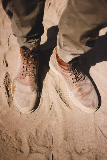 Legs of traveler in dirty boots standing on sand — Stock Photo