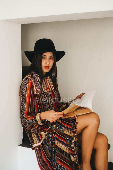 Attractive young female in stylish hat and dress looking at camera while sitting on steps and reading fashion magazine — Stock Photo