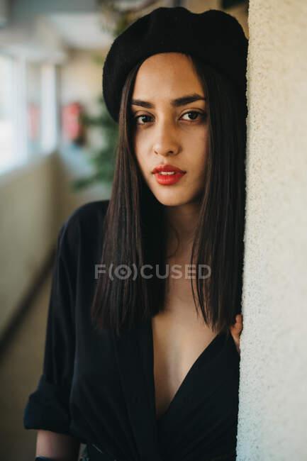 Jolie jeune femme en béret noir regardant la caméra tout en s'appuyant sur le mur à la maison — Photo de stock