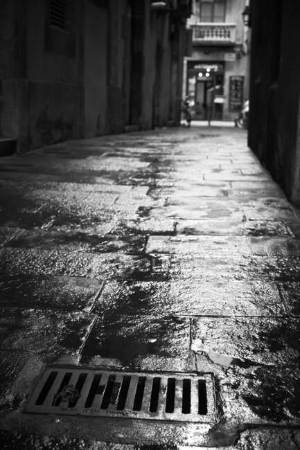 Empty narrow road wet after rain with hatch on surface in black and white colors — Stock Photo