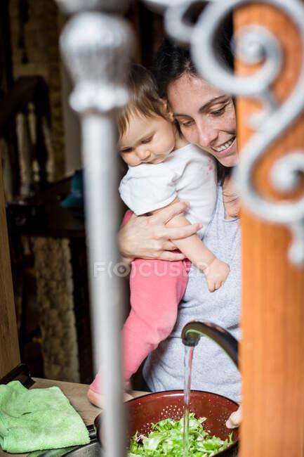 Vue à travers les bars sur la fenêtre de la femme souriante tenant bébé sur les mains et lavant la salade dans l'évier à la maison — Photo de stock