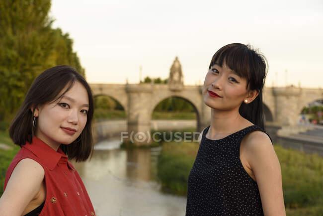 Junge Asiatinnen nahe Zaun in Park — Stockfoto