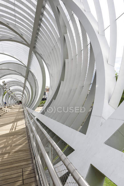 Metal structure encircling wooden path on sunny day in park — Stock Photo