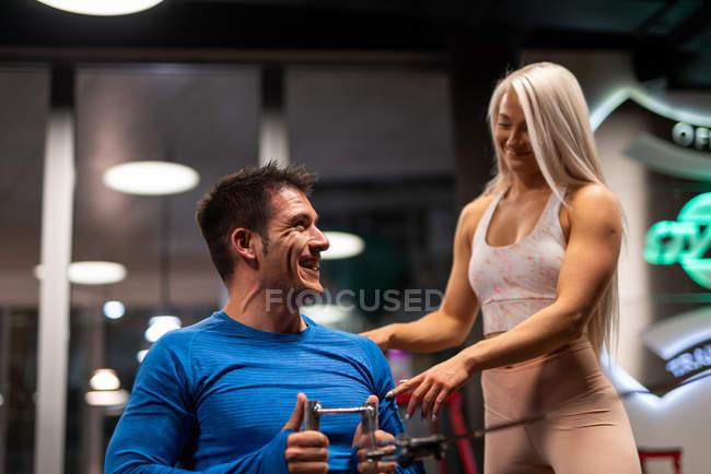 Homme, faire de l'exercice dans la salle de gym avec femme debout et souriant — Photo de stock