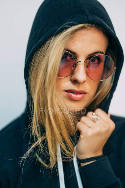 Young blond woman in sunglasses looking at camera — Stock Photo