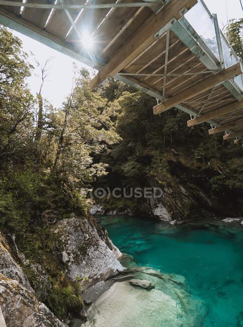 Narrow lumber bridge crossing amazing mountain river on sunny day in Blue Pools, New Zealand — Stock Photo