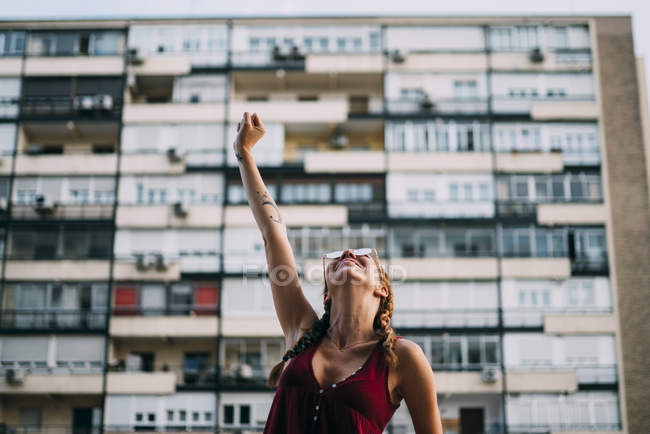 Pretty red-haired girl with braids and sunglasses standing against residential building — Stock Photo