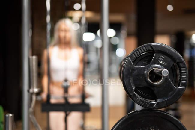 Крупный план железного гантели в тренажерном зале и женщины в спортивной одежде, делающей упражнения на заднем плане — стоковое фото