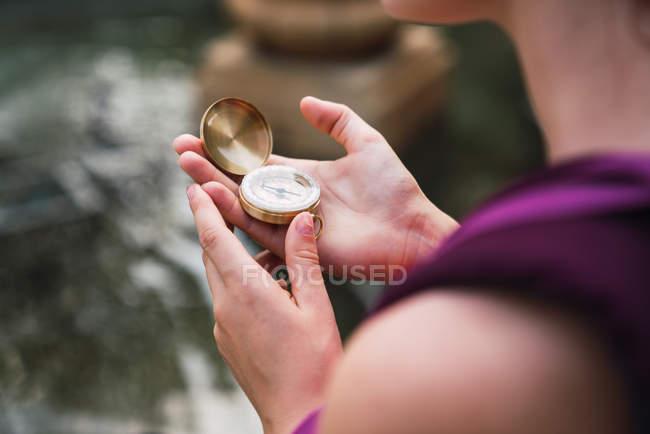Primo piano delle mani femminile che tengono bussola vicino al lago — Foto stock