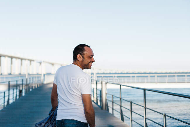 Visão traseira do macho adulto em roupa casual sorrindo e olhando para longe enquanto caminhava no cais perto do mar — Fotografia de Stock