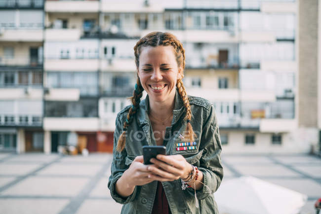 Laughing red-haired girl with braids using mobile phone against residential building — Stock Photo