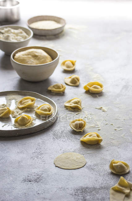 Raw tortellini in flour on grey tabletop — Stock Photo