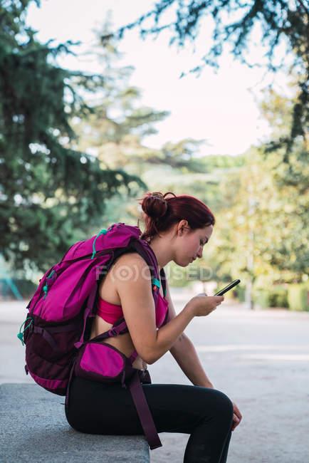 Deportiva con mochila de navegación smartphone en el parque - foto de stock
