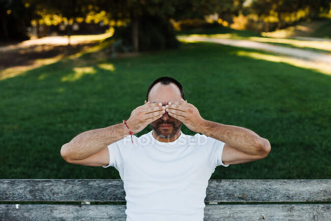 Attractive adult male covering eyes while sitting on bench in park on sunny day — Stock Photo