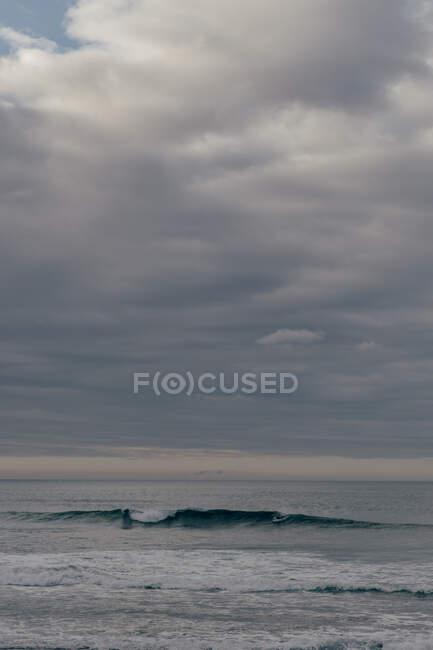 Grandes olas bajo el cielo nublado - foto de stock