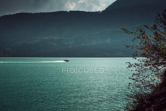 Side view of launch sailing on water between picturesque view of mountains in Austria — Stock Photo