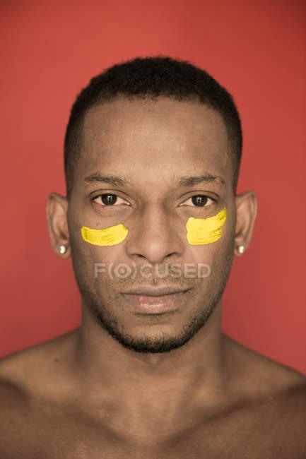 Ritratto di uomo afroamericano con macchie gialle di vernice sul viso — Foto stock
