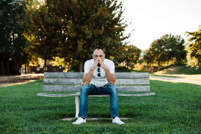 Attrayant adulte mâle couvrant la bouche tout en étant assis sur le banc dans le parc le jour ensoleillé — Photo de stock