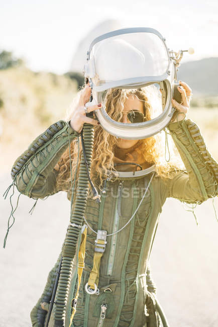 Confident woman in astronaut costume putting on helmet in sunlight — Stock Photo