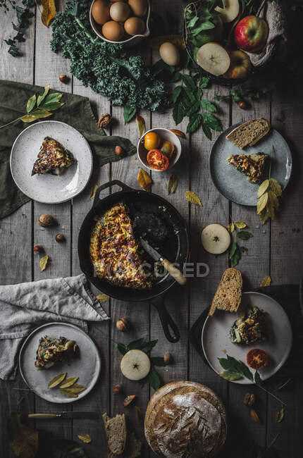 From above view of tasty fresh tortilla on pan near plates with slices, tomatoes, fruits, nuts and leaves on wood board — Stock Photo