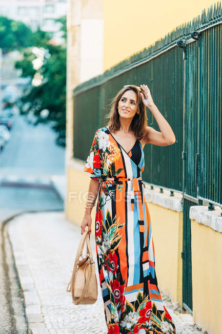 Modern woman in long dress carrying handbag and walking on street in sunlight — Stock Photo