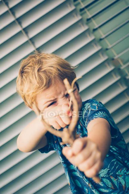 Блондинка маленький хлопчик у футболку гра з рогатки проти шторки — стокове фото