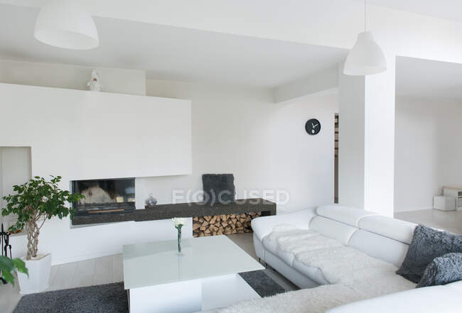 Modern living room made in white color furnished with cozy leather couch and table with lamps hanging on ceiling — Stock Photo