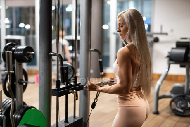 Fit attractive woman in sportswear doing exercise in gym — Stock Photo
