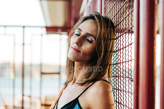Заспокоїти жінку з закритими очима, спираючись на металеву дріт огорожі на відкритому повітрі — стокове фото