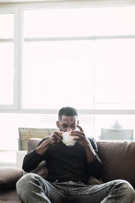 Замислений чорношкірий розслабляючий на дивані з кавою — стокове фото