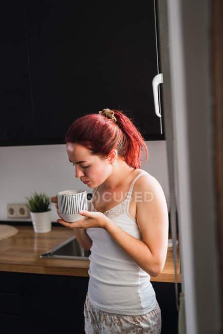Giovane donna che beve caffè in cucina — Foto stock