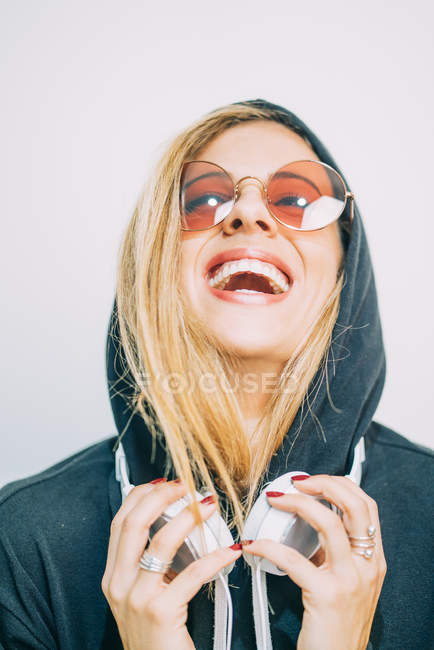 Young blond woman in sunglasses and hoodie with headphones laughing on white background — Stock Photo