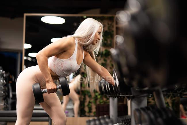 Спортивная блондинка с гантелями в тренажерном зале — стоковое фото
