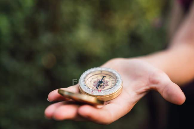Primo piano della mano femminile che tiene la bussola in natura — Foto stock