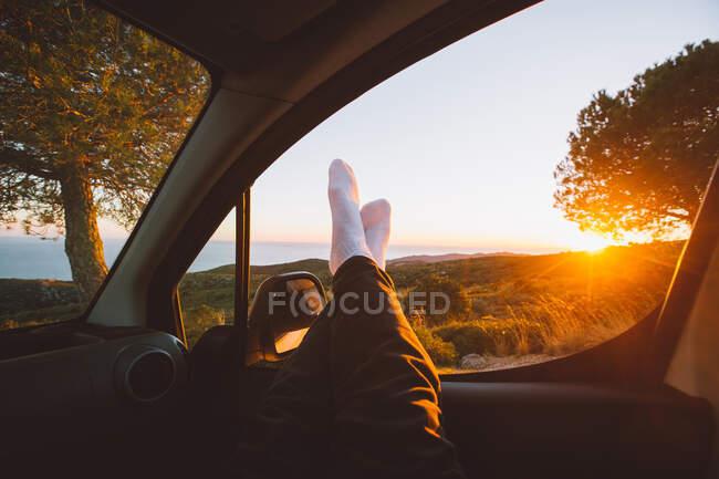 Обрезать ноги в машине на закате — стоковое фото