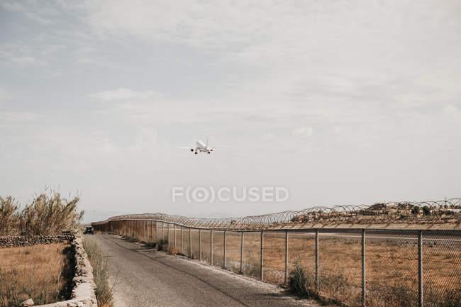 Aerei che sale dall'aeroporto racchiuso da filo di sicurezza vicino a strada con auto a Mykonos — Foto stock