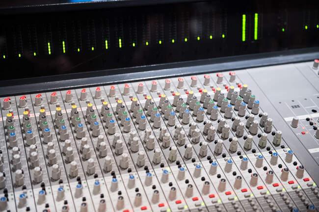 Primer plano de los interruptores en la placa mezcladora de audio profesional en el estudio de grabación - foto de stock