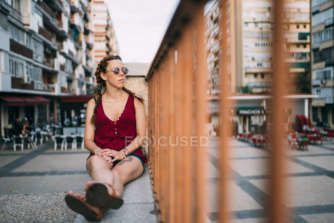 Thoughtful red-haired girl with braids and sunglasses sitting near railing in city — Stock Photo