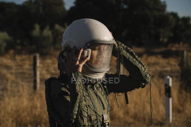 Female astronaut checking helmet in nature — Stock Photo