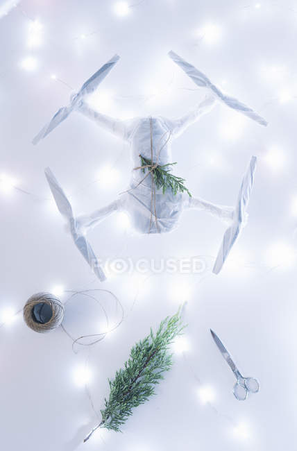 Drone wrapped as Christmas gift with fir branch on white illuminated background — Stock Photo