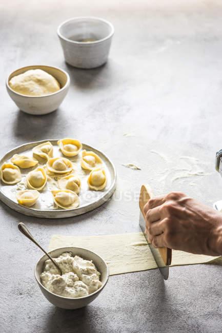 Человеческая рука, подготовка тортеллини с сыром на серый настольные — стоковое фото
