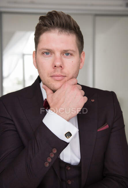 Young handsome man in black formal costume and white shirt with stylish hairdo sitting in room and looking at camera with hand on chin — Stock Photo