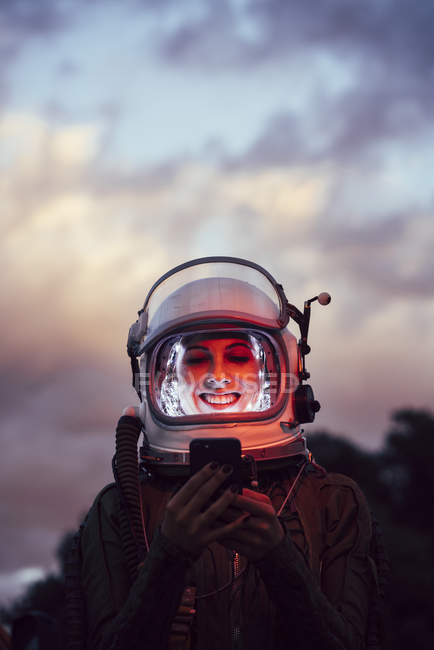 Female astronaut in illuminated vintage helmet with mobile phone standing in nature at sunset — Stock Photo